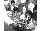 Members of a Samaritan family in Palestine are gathered for their Passover feast round the dish of lamb seasoned with bitter herbs. An early photograph.