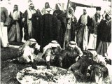 Villagers who have been invited to a feast by a wealthy sheik. Guests eat in relays and the common dish is frequently refilled as the feast progresses. An early photograph.