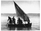 A early photo taken at daybreak on the Sea of Galilee. The boatmen handle long drag nets, put out at night, usually on deep water.